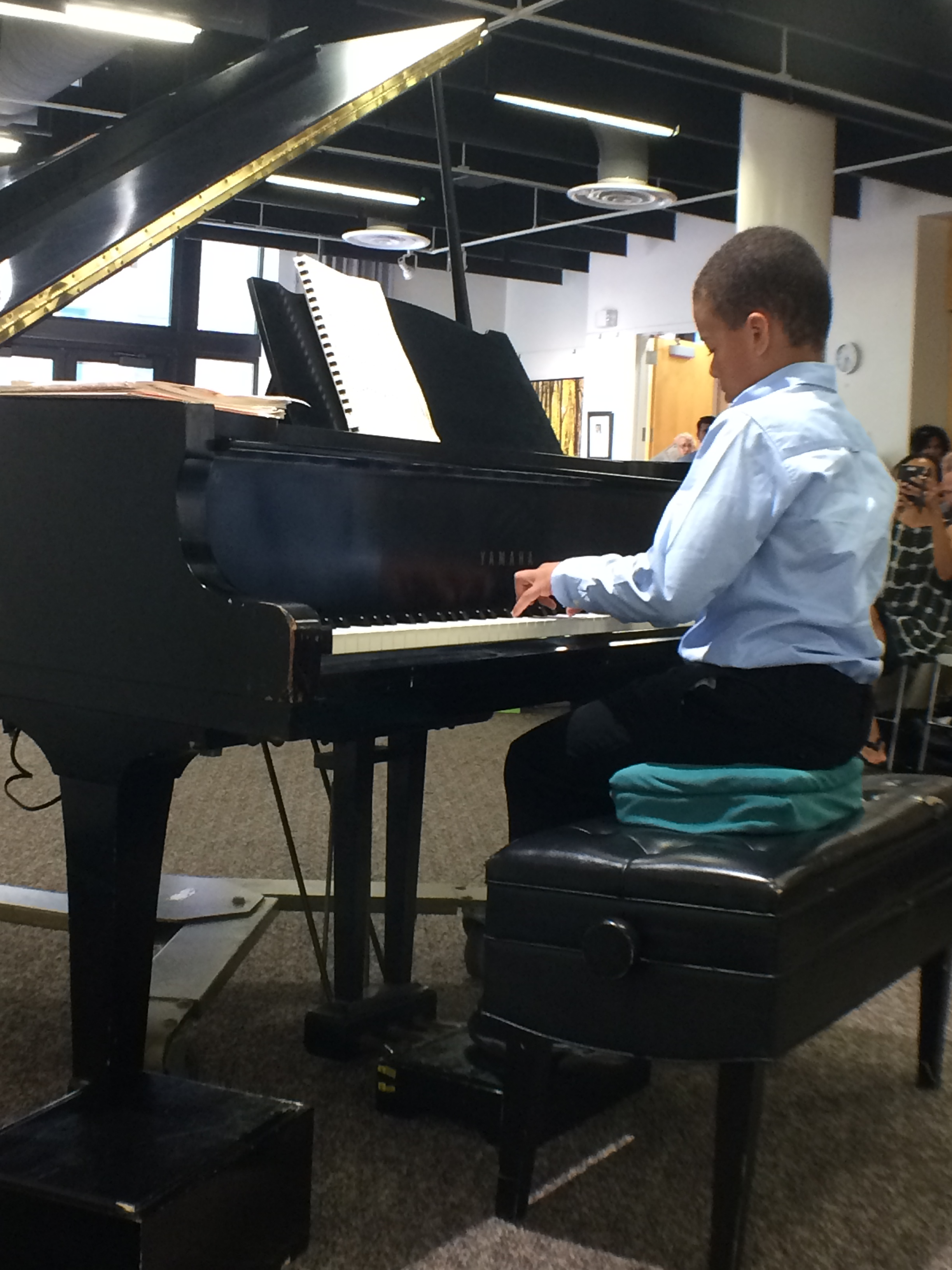 A male student playing the piano solo