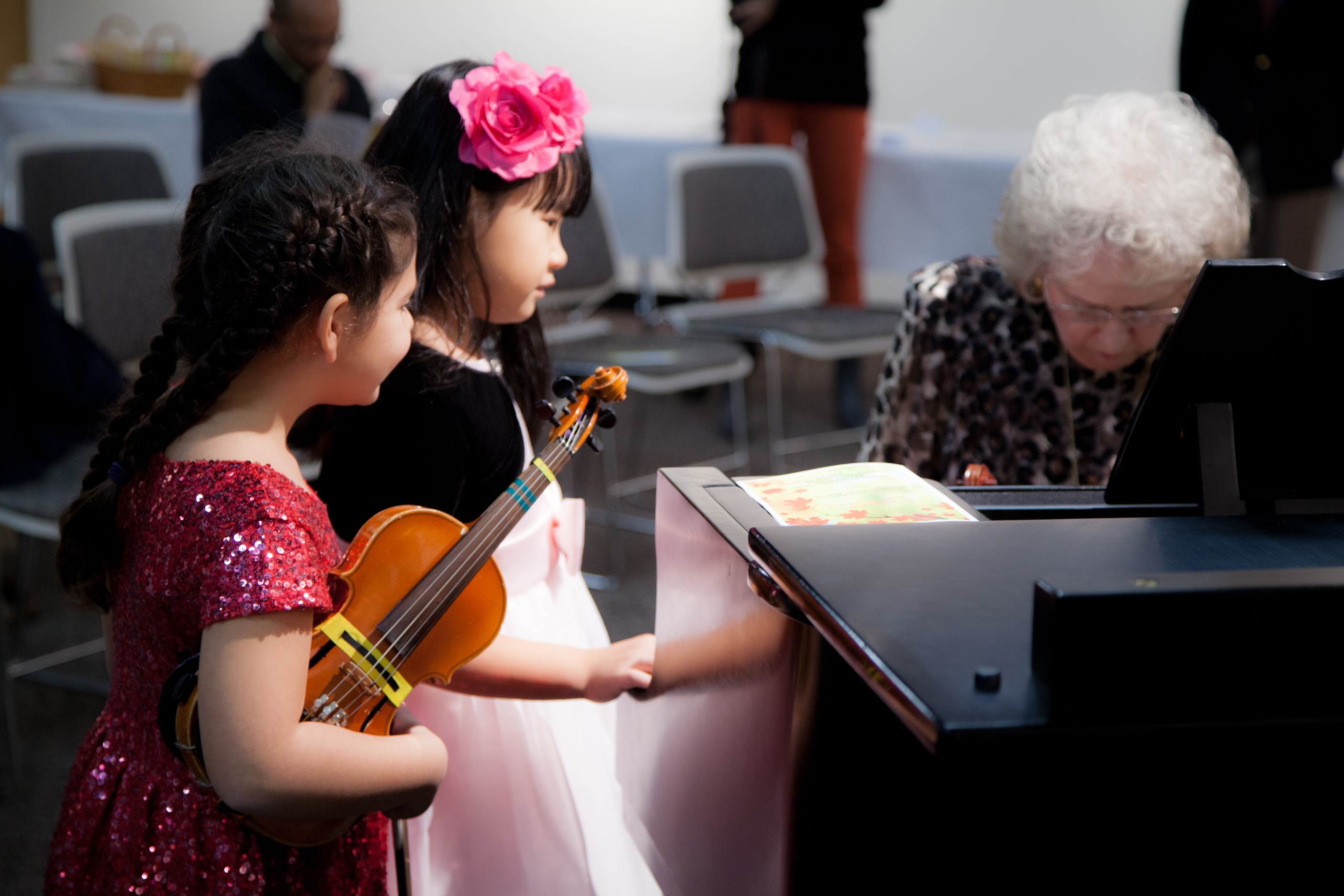 2 female students watching their teacher play piano