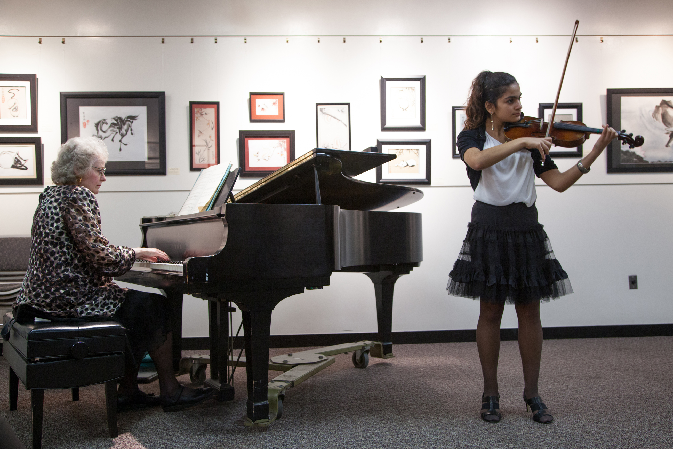 A female playing the violin next to a piano