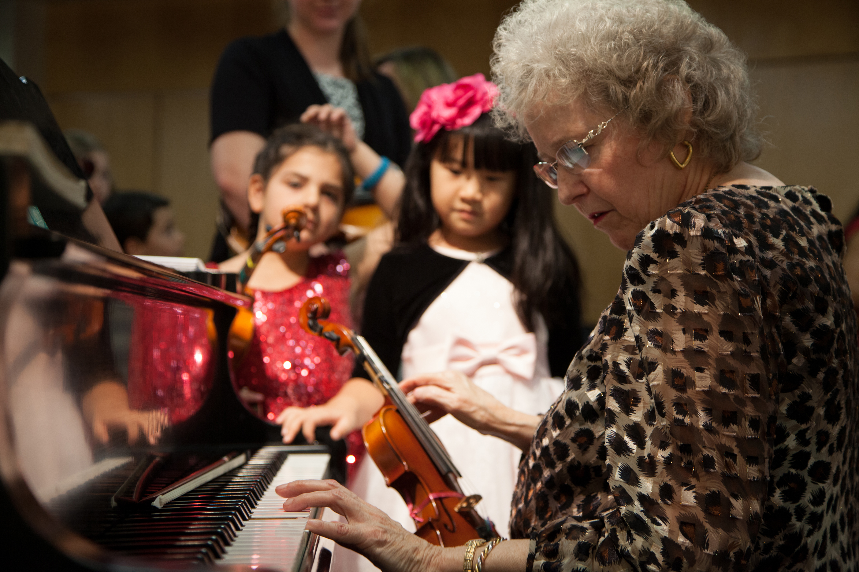A teacher playing the piano for 2 female students